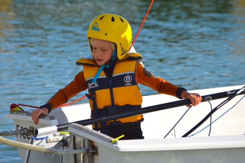 A young boy holding the stick of a dinghy