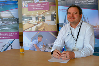 A UKSA sailing instructor sat in front of a display about sailing training and career opportunities.