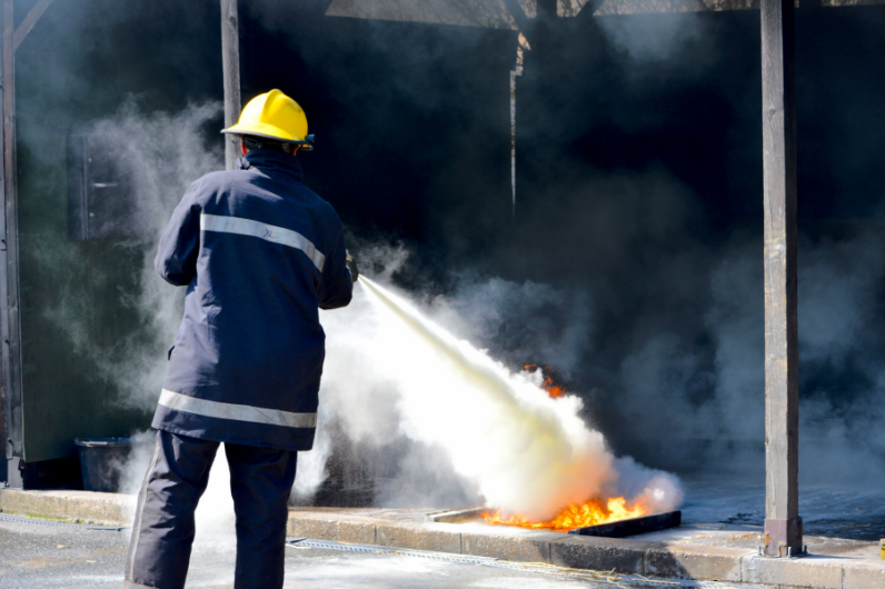 A student using a fire extinguisher on the Advanced Fire Fighting Course