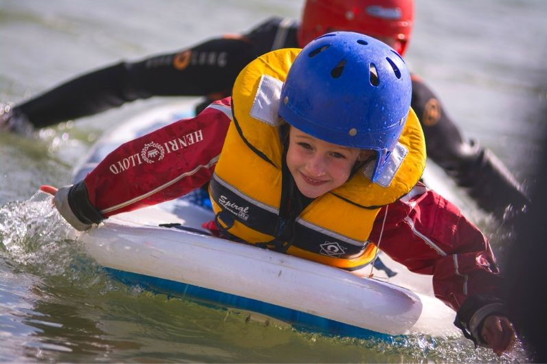 a young child on the front of a paddleboard smiling