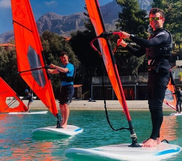 Two students in Greece learning to windsurf