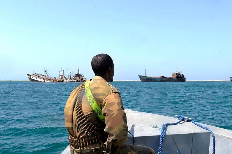 A Somali pirate with a gun onboard a boat
