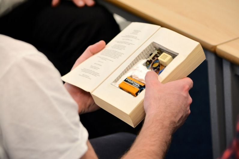 A student opening a book with an electronic device inside