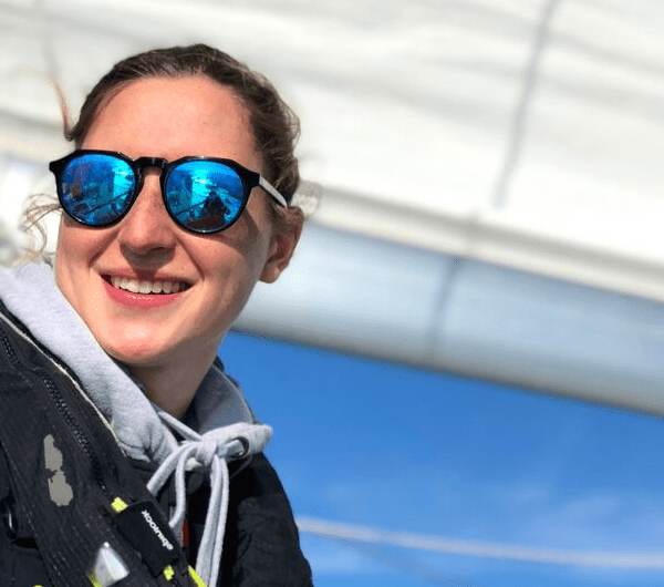 A young female sailor smiling whilst looking out to sea