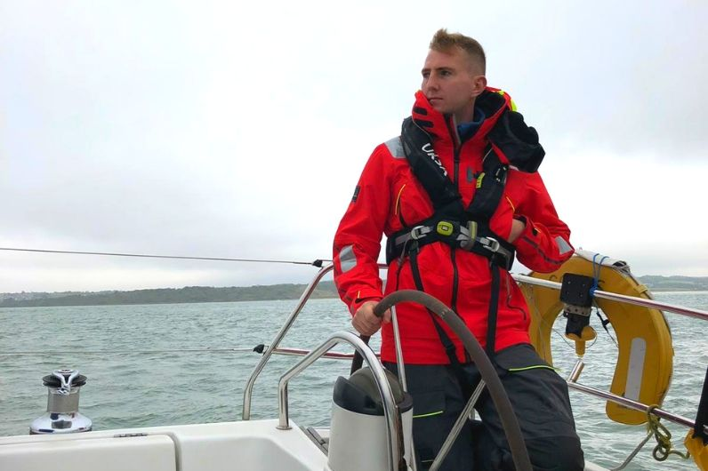 A UKSA professional yachting trainee uses the wheel to steer a vessel during a sailing training course.