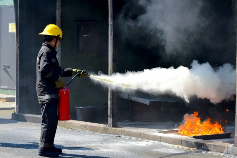 A student using a fire extinguisher on open flames