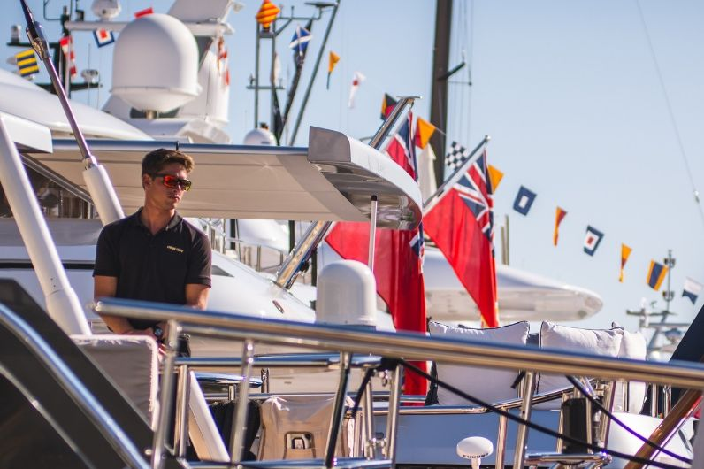 A UKSA professional sailing trainee standing on the deck of a superyacht.