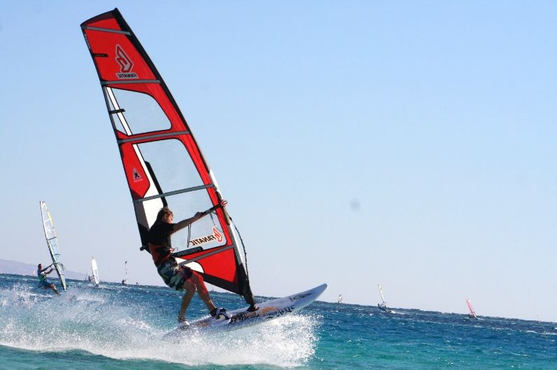 A student learning how to windsurf in open water