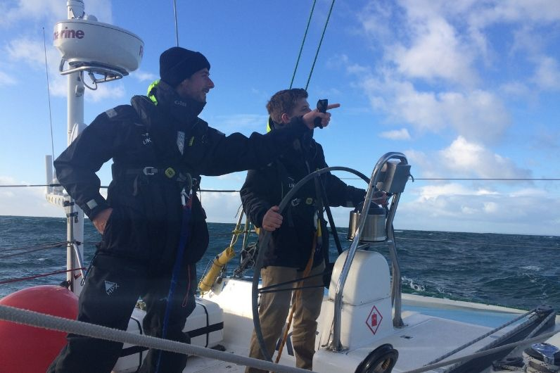 Senior instructor directing a student onboard a yacht