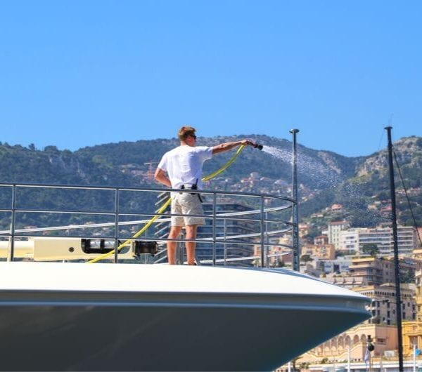 Deck crew washing a motor yacht