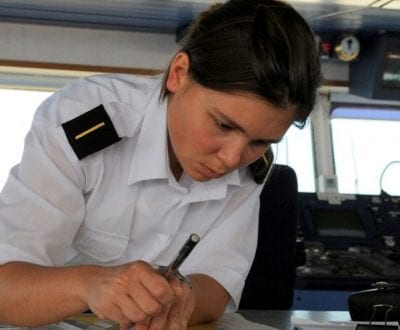A female officer plotting a course on her chart