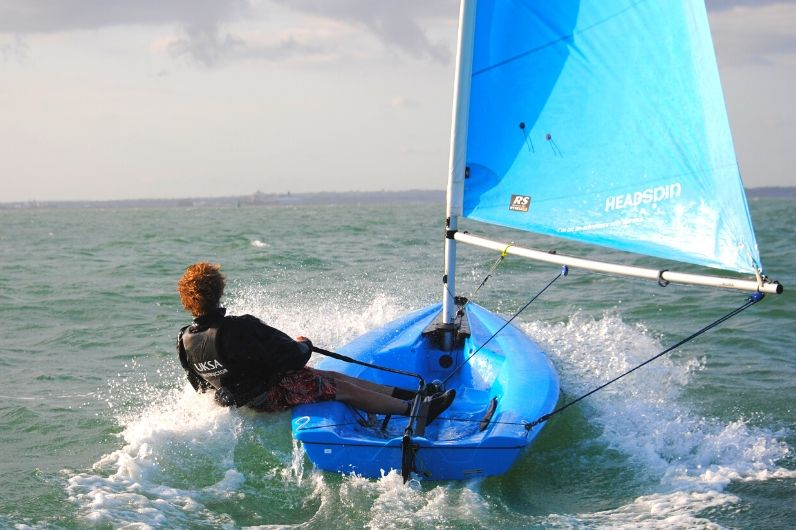 A male sailing a dinghy on the Solent