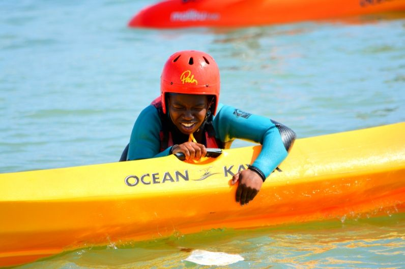 A young female students trying to overturn a kayak