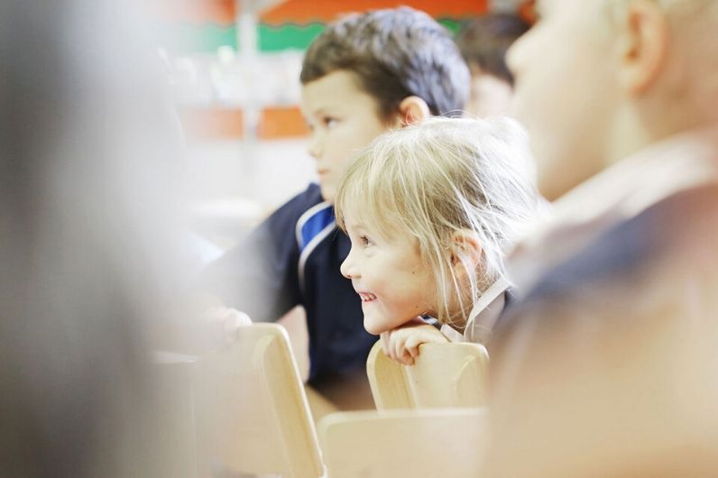 A school child smiling whilst in class