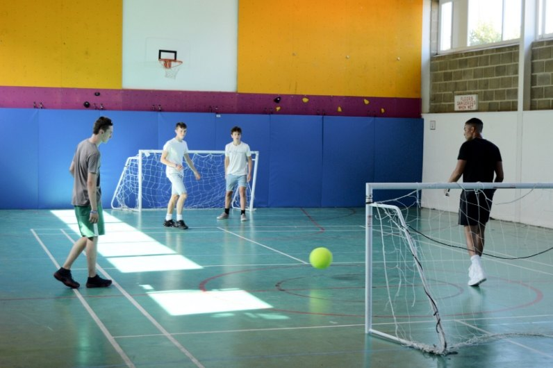 4 Males playing football inside a sports hall