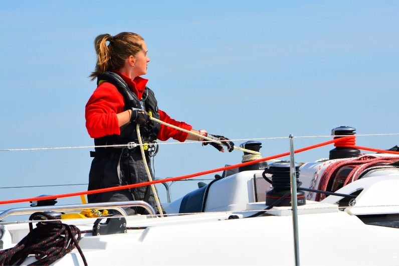 A female yachtmaster student pulling on the yacht's ropes
