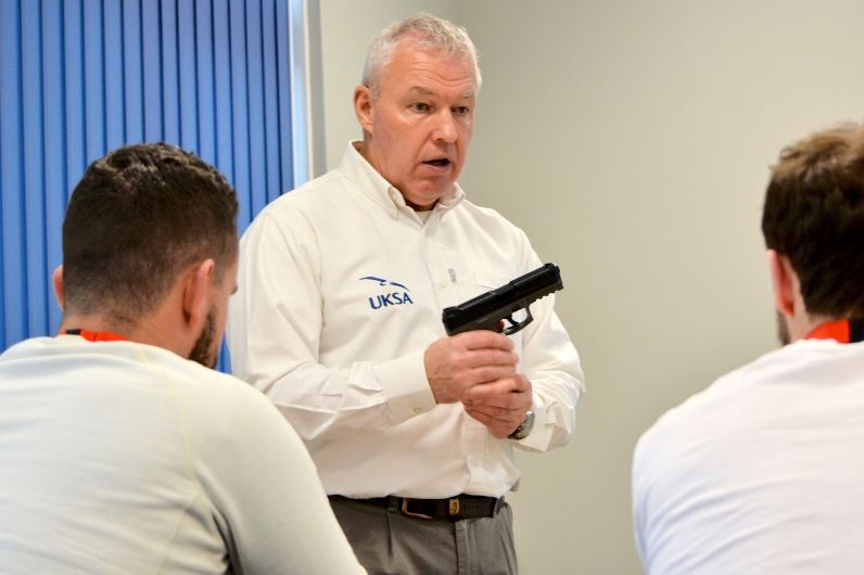 An instructor with a training device teaching students