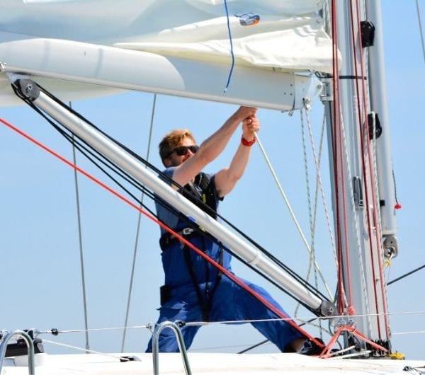A student pulling on the sail ropes