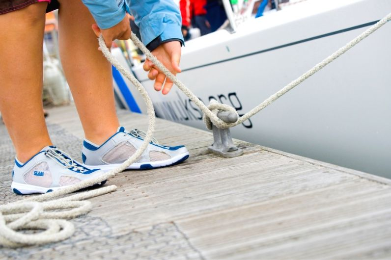 A sailor with UKSA learning to tie a yacht rope to a dock cleat using a cleat hitch knot.