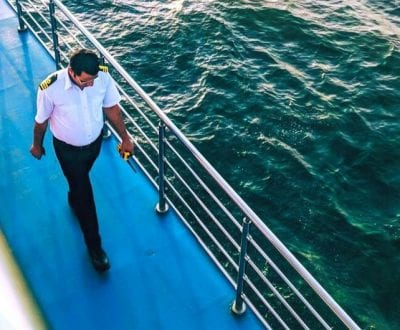 The captain of a superyacht walking the dek
