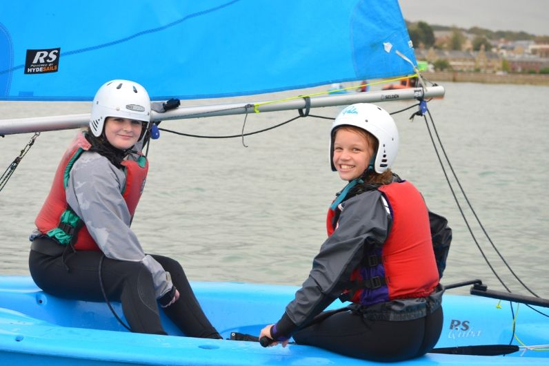 Two students having fun onboard a dinghy