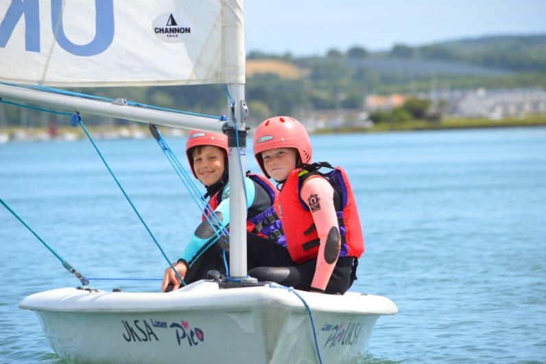 Two students sat on the side of a dinghy