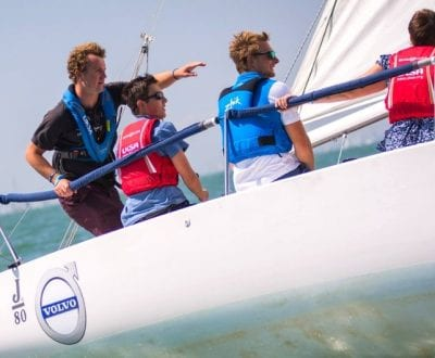 A UKSA trained instructor on a yacht giving advice to trainee sailors.