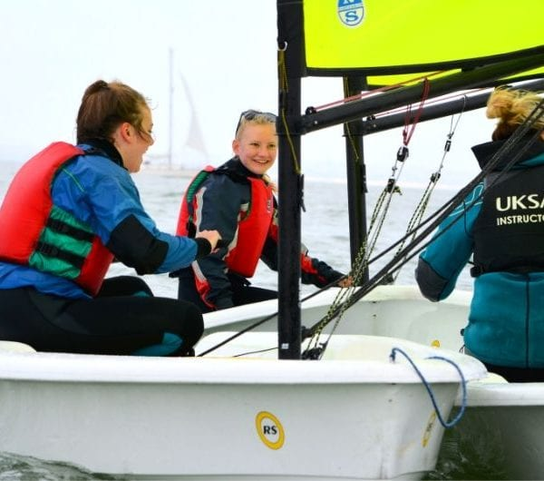 Students learning how to dinghy sail with an instructor