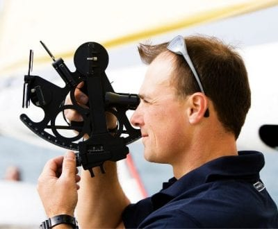 A male using a sextant for use in navigation