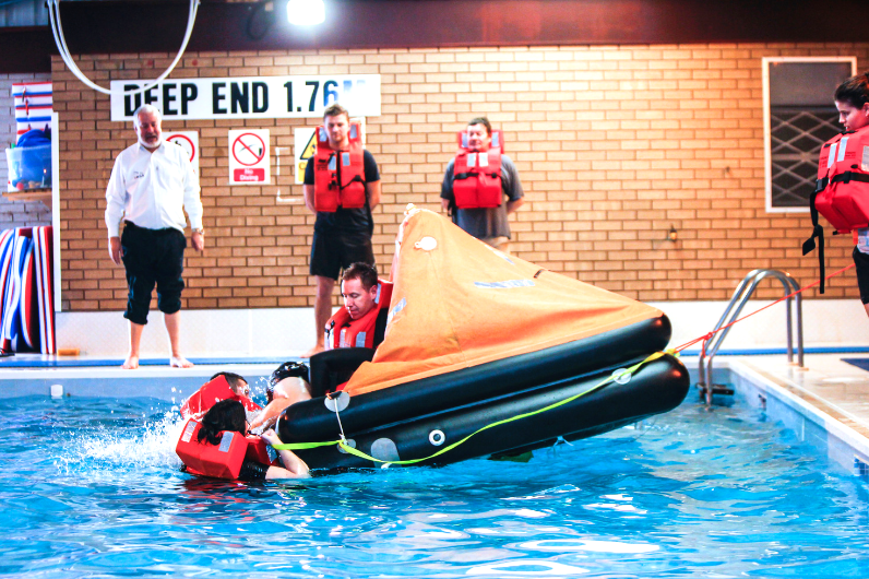 Students inflating a survival craft on the Personal Survival Techniques Course