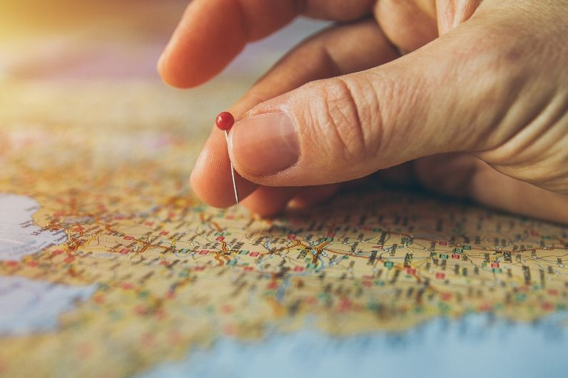 Hand pin pointing a location on a world map