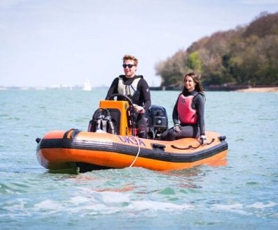 Power boat or rib stationary on water with two people on board