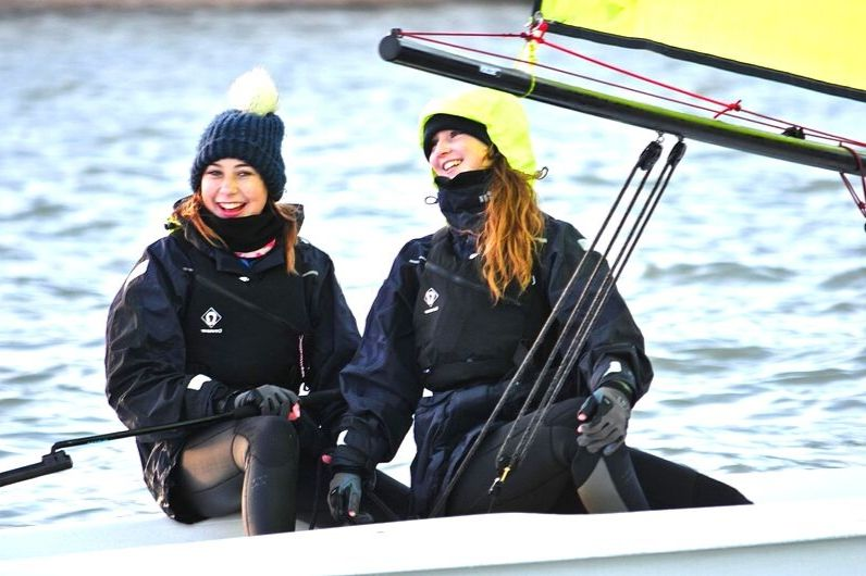 Two girls smiling and laughing onboard a dinghy at UKSA