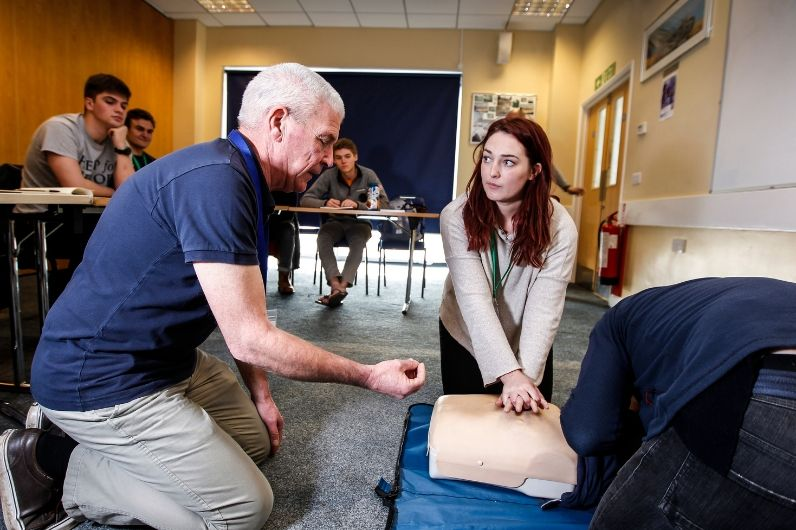 As part of the UKSA's maritime safety training, an instructor advises a trainee how to carry out life-saving first aid on a resuscitation manikin.