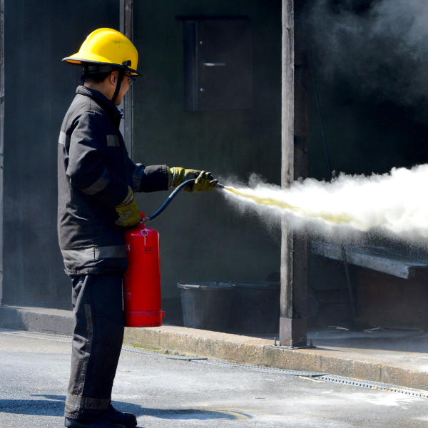 A man extinguishing a fire using fire fighting equipment
