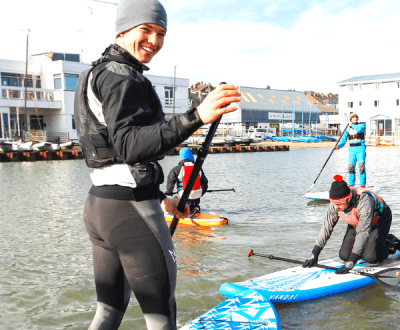 An instructor on a paddleboard smiling