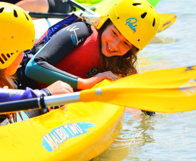 A young girl in a kayak with her hand in the water