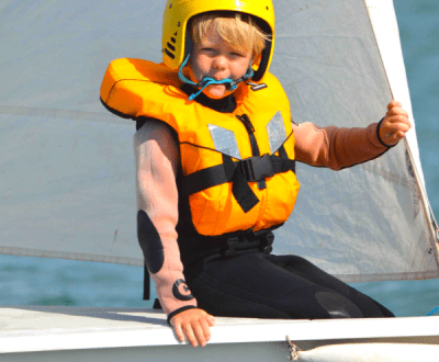 A young child wearing a yellow life jacket