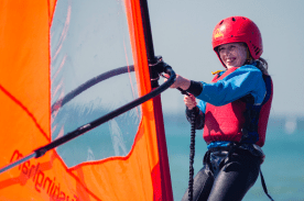 A child smiling whilst learning to windsurf