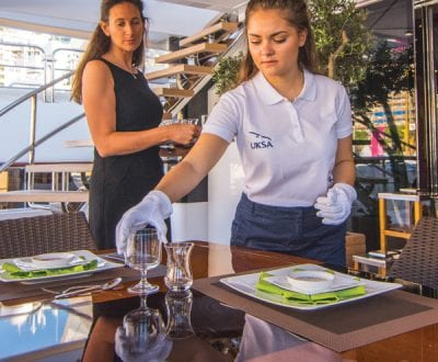 A Superyacht stewardess placing a glass under the eye of an instructor