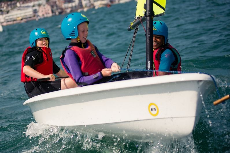School children learning to sail a dinghy sailing boat
