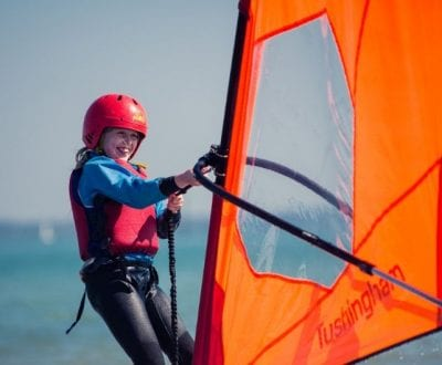 A school child holding up their windsurfing sail