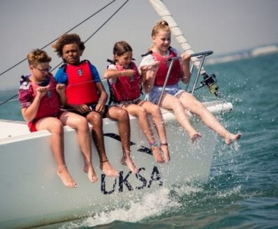 Young children sitting on the bow of a yacht enjoying the waves