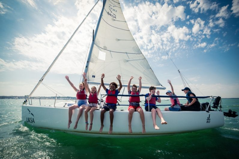 A group of school children sitting on the side of a yacht waving