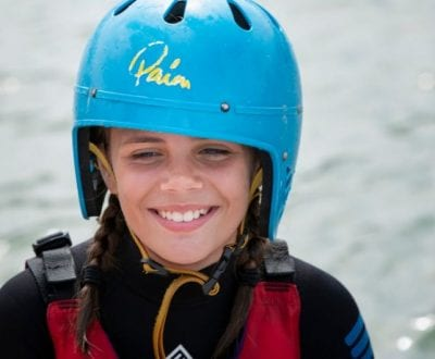 A school child smiling whilst wearing a wetsuit and helmet