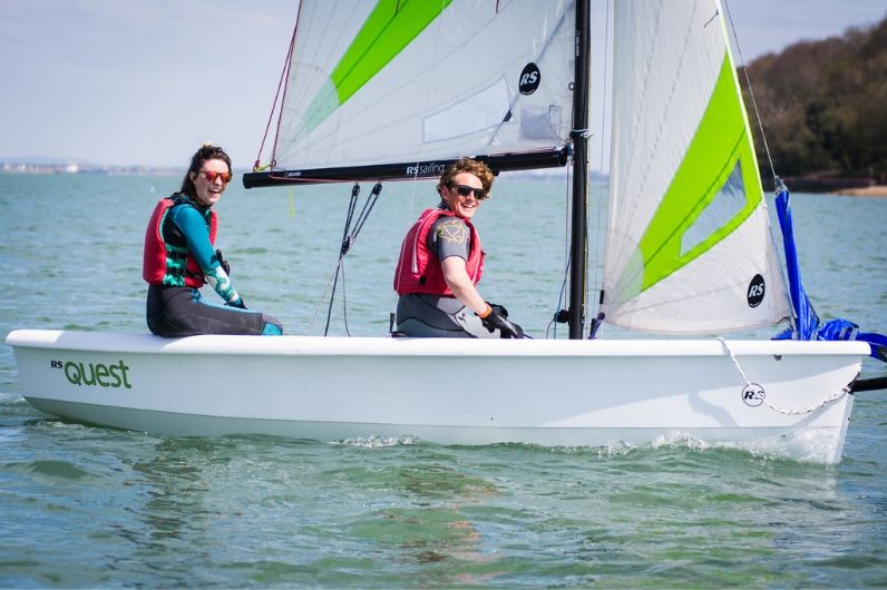 Two young adults at sea in a sailing dinghy boat