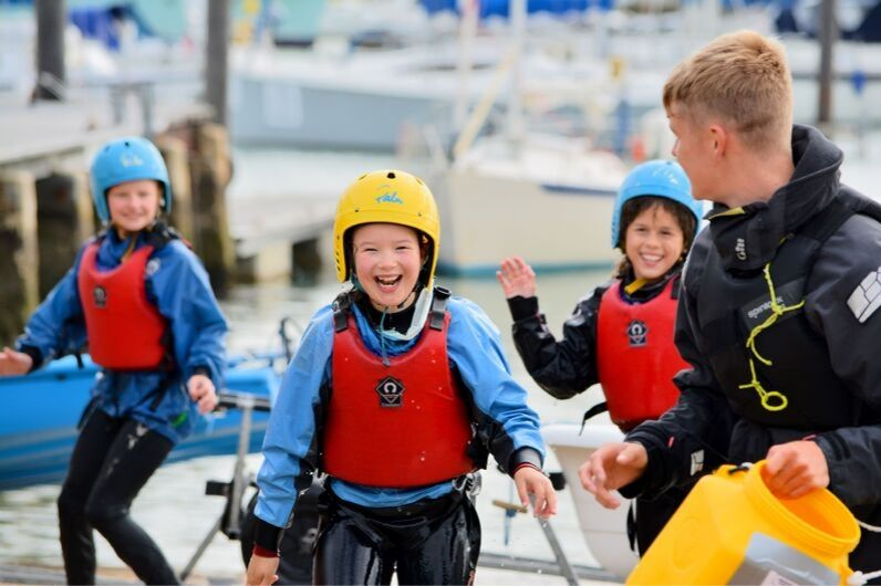 Children smiling with a UKSA instructor