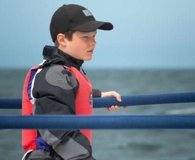 A young boy holding on the rails onboard a keelboat