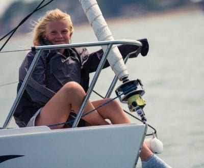 A young child sitting at the bow of a keelboat