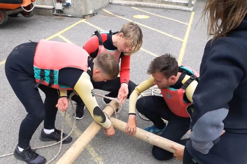 A group of young males building a raft